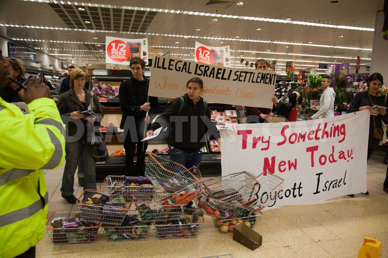 Human rights activists hold banners explaining that they have erected a symbolic illegal Israeli settlement in the Sainsbury's supermarket; Israel's West Bank settlements are illegal under international law.