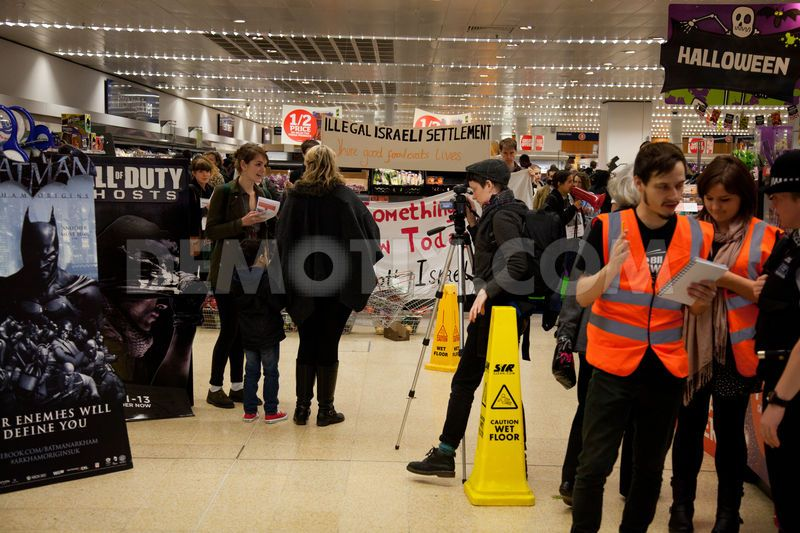 Human rights activists explain the purpose of the protest inside the Sainsbury's supermarket to interested members of the public.