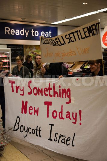 Activists held banners using clever human rights-oriented spins on Sainsbury's marketing slogans such as 'Good food costs less' and 'Try something new'.