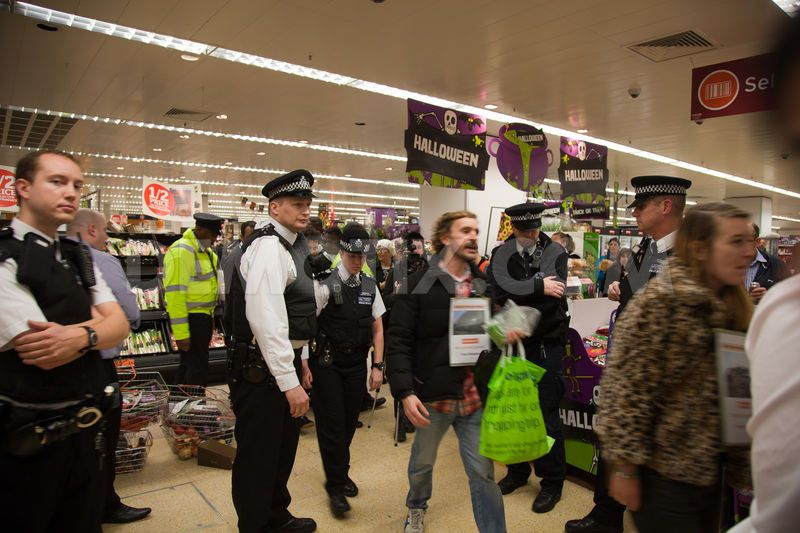 Human rights activists chant pro-Palestinian slogans as police ask them to leave the Sainsbury's supermarket.