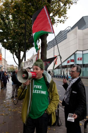 Protesters outside the Sainsbury's supermarket in Islington, London, wave Palestinian flags and use loud hailers to explain the purpose of the protest to passing members of the public.