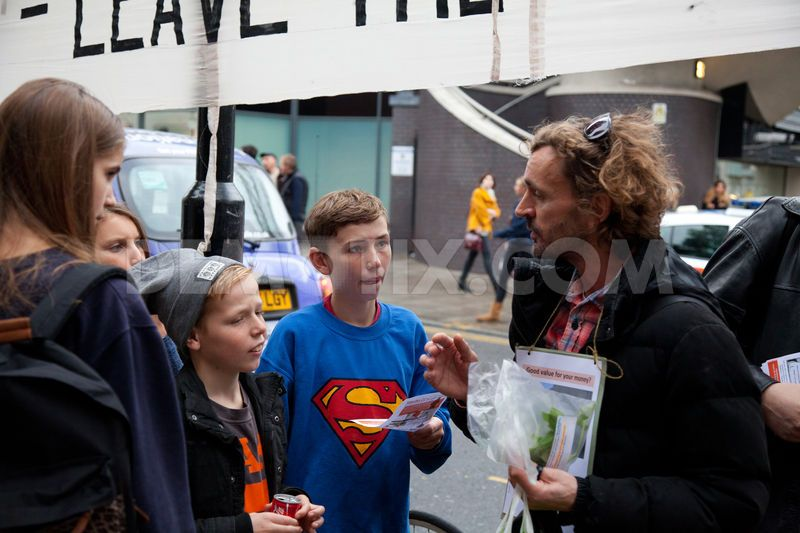 A human rights activist holding ethically-sourced Co-operative supermarket herbs explains the purpose of the protest at Sainsbury's to interested young members of the public.