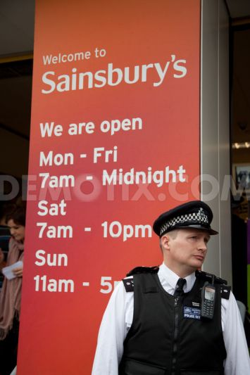 A police officer observes the protest taking place outside the large Sainsbury's supermarket in Islington, London.